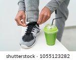 fitness man tying running shoes ... | Shutterstock . vector #1055123282