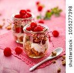 granola with fresh raspberries... | Shutterstock . vector #1055277398