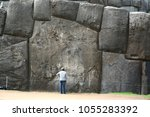 The gigantic boulder of Sacsayhuaman show the scale of it with human being. It perfectly fitted together with other stones. This is the Inca ruin located on the mountain top next to Cuzco, Peru