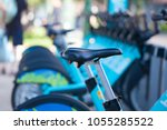 row of blue bikes parked on... | Shutterstock . vector #1055285522