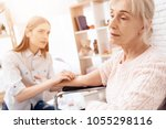 girl is nursing elderly woman... | Shutterstock . vector #1055298116