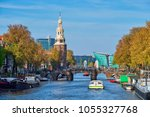 Small photo of Amterdam cityscape with canal boats and medieval houses and NEMO Science museum and Montelbaanstoren Tower. Amsterdam, Netherlands