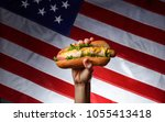 Stock photo classic american hot dog in hand on american flag background 1055413418