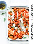 Baking tray filled with delicious juicy oven roasted red tomatoes with fresh sage leaf herb and olive oil - stock photo