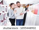 smiling family choosing ceramic ... | Shutterstock . vector #1055448902