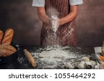 man preparing buns at table in... | Shutterstock . vector #1055464292