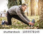 sporty man stretching legs in... | Shutterstock . vector #1055578145