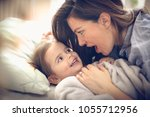 young mother with her little... | Shutterstock . vector #1055712956