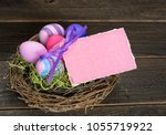colorful easter eggs in nest on ... | Shutterstock . vector #1055719922