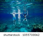 Small photo of Underwater photo of three young playful adventuristic handsome student friends diving and swimming with goggles and snorkelling mask in the exotic turquoise sea at summer vacation.