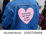 Small photo of MILAN - FEBRUARY 21: Woman with blue jeans jacket with pink heart with 'Nothing better than pizza' motto before fashion Albino Teodoro show, Milan Fashion Week street style on February 21, 2018
