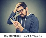 Small photo of Confused stressed man looking at too many credit cards full of debt