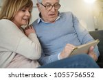 senior couple in sofa...   Shutterstock . vector #1055756552