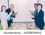 four smiling at camera business ... | Shutterstock . vector #1055834942