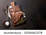 grilled t bone steak on stone... | Shutterstock . vector #1056062378