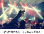 raised beer glass at a concert. | Shutterstock . vector #1056385466