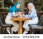 muslim women using smartphones | Shutterstock . vector #1056386246