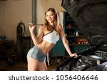 female machanic leans on a car... | Shutterstock . vector #1056406646