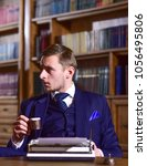 Small photo of Man in suit with busy face in library with antique books on background, defocused. Retro writer concept. Writer or author with typewriter looks for inspiration for new book, drinks coffee in library.