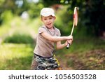 boy in a white cap playing... | Shutterstock . vector #1056503528