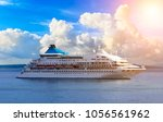 Luxury cruise ship sailing against background of beautiful clouds and Rhodes island in the distance