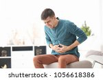 young man suffering from... | Shutterstock . vector #1056618386