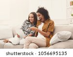two happy female friends using... | Shutterstock . vector #1056695135