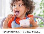 toddler sitting in highchair... | Shutterstock . vector #1056759662