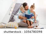 family father reading to... | Shutterstock . vector #1056780398