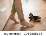 tired woman touching her ankle  ... | Shutterstock . vector #1056808895