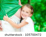 Beautiful little girl hugging a pregnant mother's belly - stock photo