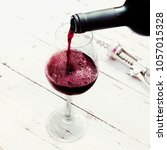 pouring red  wine from bottle... | Shutterstock . vector #1057015328