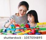 little girl playing wooden... | Shutterstock . vector #1057054895