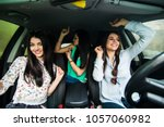 three girls driving in a car... | Shutterstock . vector #1057060982