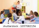 cheerful female teacher giving... | Shutterstock . vector #1057082156