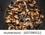 fried champignons in a frying... | Shutterstock . vector #1057089212