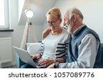 senior couple using a laptop... | Shutterstock . vector #1057089776