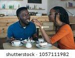 african american woman feeding... | Shutterstock . vector #1057111982