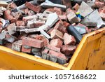 Small photo of Yellow metal skip full of old bricks