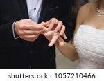 groom holding bride's finger... | Shutterstock . vector #1057210466