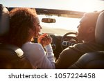 couple driving look at each... | Shutterstock . vector #1057224458