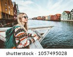 Young blonde woman traveling in Trondheim city Norway vacations weekend Lifestyle outdoor girl tourist with backpack sightseeing scandinavian architecture alone