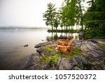 adirondack chairs on a rock... | Shutterstock . vector #1057520372