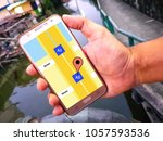 Small photo of hand holding Mobile phone at outdoors on the Canal background. with Check in road map, Position. concept:GPS,navigator