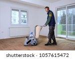 sanding hardwood floor with the ... | Shutterstock . vector #1057615472