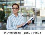 business woman holding... | Shutterstock . vector #1057744535