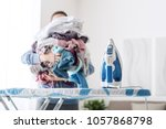 housewife bringing a huge pile... | Shutterstock . vector #1057868798