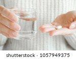 woman's hands holding a glass... | Shutterstock . vector #1057949375
