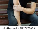 elbow pain. man in the park... | Shutterstock . vector #1057991615