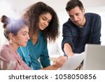 in the office. a young multi... | Shutterstock . vector #1058050856